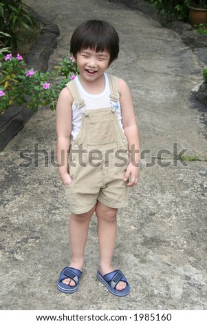 Little boy smiling and standing at the garden - stock photo