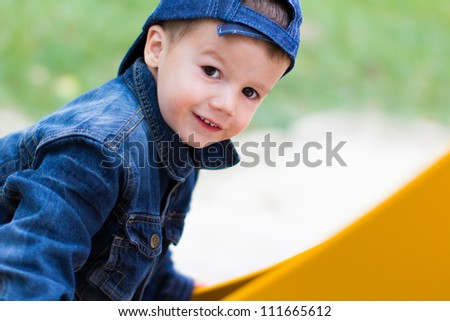 Little boy smiling on slide - stock photo