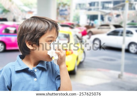 Little boy sneezing cause allergic on the road - stock photo