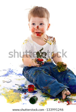 little boy stained in paint on white background - stock photo