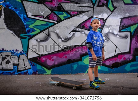 Little boy standing in front of vibrant graffiti in a trendy blue outfit looking at the camera with his skateboard on the ground behind him - stock photo