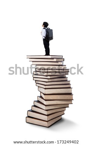 Little boy standing on a stack of books isolated on white background - stock photo