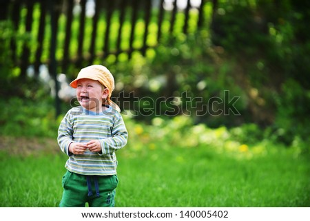 little boy standing on  lawn and crying
