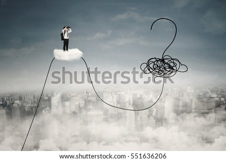 Little boy standing on the cloud and using binoculars for looking at a question mark and chaos symbol on the sky