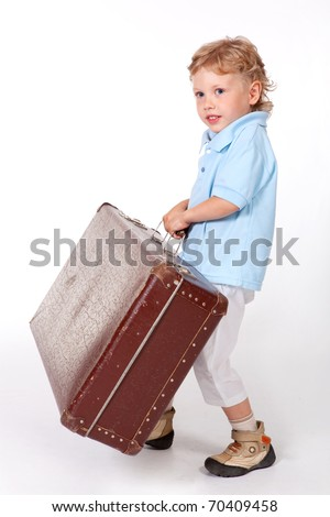 Little boy standing with a suitcase in his hand. Travel or relocation.