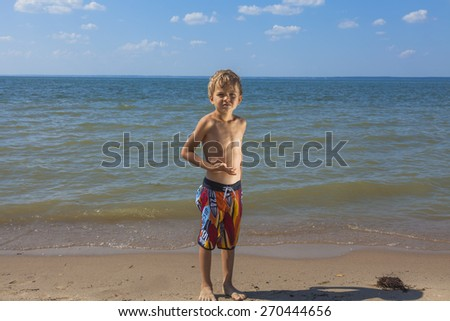little boy staying on the sunny beach - stock photo