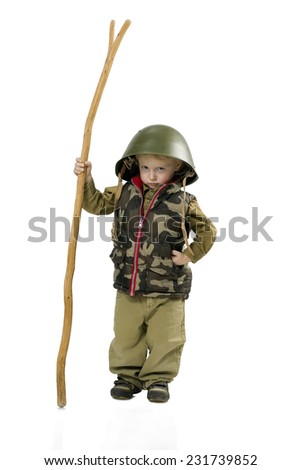Little boy stern soldier in camouflage and a large helmet on a white background. In his hands he holds a staff. - stock photo