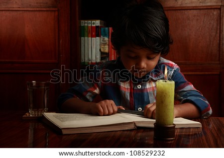 Little boy studying in low light with a burning candle - stock photo
