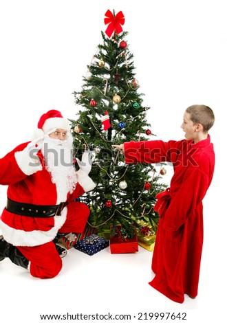 Little boy surprises Santa Claus on Christmas morning.  Isolated on white.   - stock photo