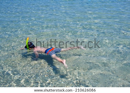 Little boy swimming in a shallow water - stock photo
