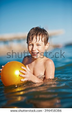 Little boy swimming in the sea or ocean with yellow ball. Kids in swimming pool. Children swim outdoors. Toddler child, kid on summer vacation playing on a beach. - stock photo