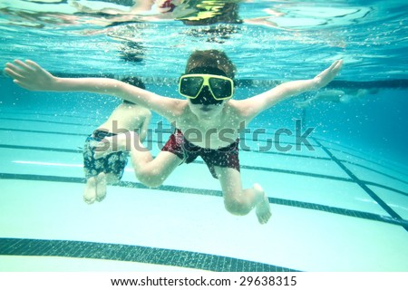 little boy swimming underwater looking at camera - stock photo