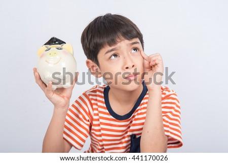 Little boy taking hammer trying to broke piggy bank - stock photo