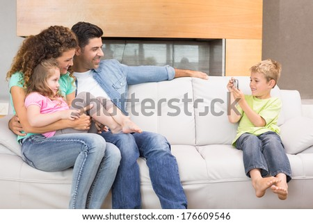 Little boy taking photo of family on the sofa at home in living room - stock photo