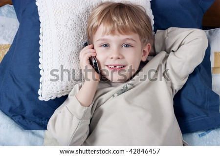 Little boy talking by mobile phone and smiling - stock photo