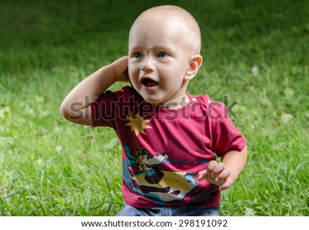 little boy talking on the phone sitting on the grass - stock photo