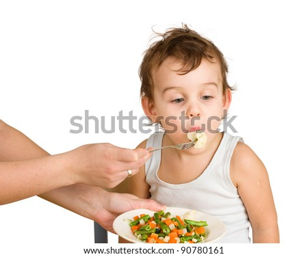 Little boy tasting vegetable salad. Isolated on white - stock photo
