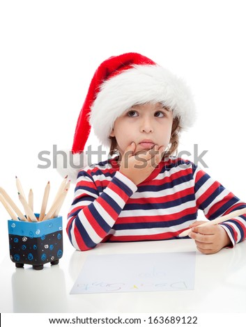 Little boy thinking about writing a letter to Santa - stock photo