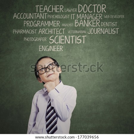 Little boy thinking an aspiration and looking up - stock photo
