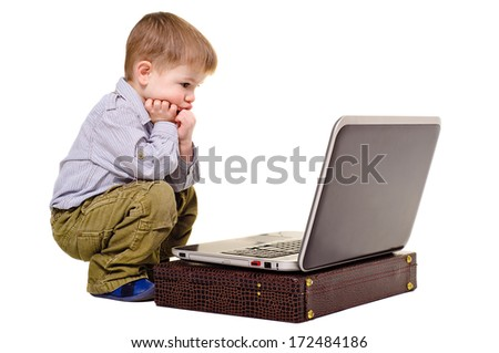 Little boy thoughtfully sits at a laptop - stock photo