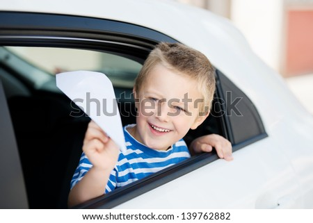 Little boy throwing a paper plane while looking out the car - stock photo
