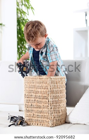 Little boy tidying up his toys in a basket