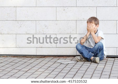 Little boy tired sad and stressed with tablet computer PC. Kid sitting on the ground, holding his head, close eyes. Casual wear. Outdoor. Education, learning, technology, addiction concept