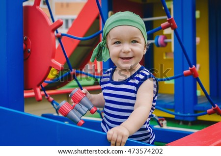 Little boy toddler playing on the playground in the form of a ship. Dressed as a sailor (pirate) in the striped vest and bandanna