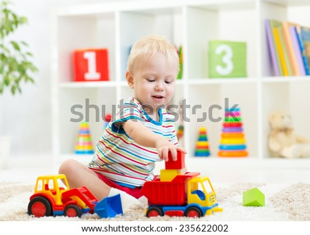 little boy toddler playing with toy car at home - stock photo