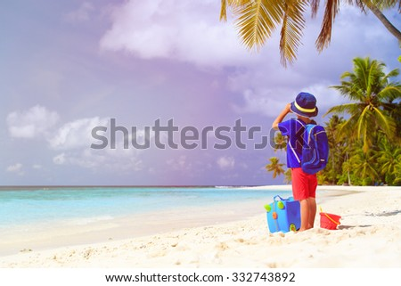 little boy travel on summer tropical beach with suitcase and binoculars - stock photo