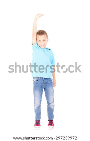 little boy trying to be taller isolated in white - stock photo