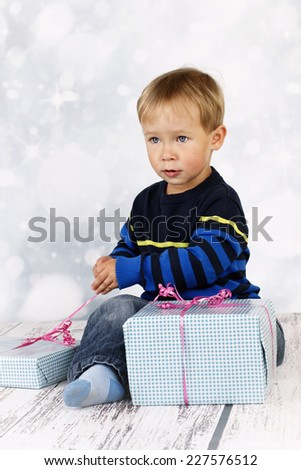 Little boy unwrapping christmas presents - stock photo