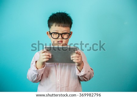 Little boy using a pad./ Child playing with digital tablet on the blue background - stock photo
