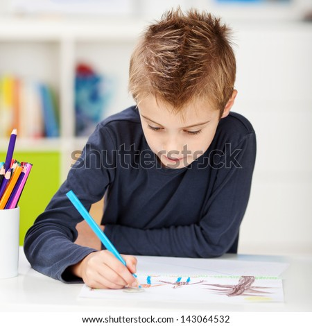 Little boy using colored pencil while drawing on paper at table in house - stock photo