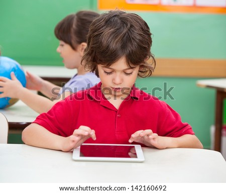 Little boy using digital tablet at desk in classroom - stock photo