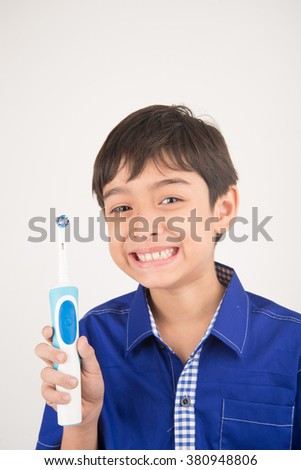 Little boy using electric toothbrushes on white background