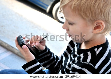 little boy using smartphone with stylus - stock photo