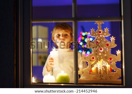 Little boy waiting for Santa by window at Christmas time and holding candle. With colorful lights from Christmas tree on background, selective focus. - stock photo