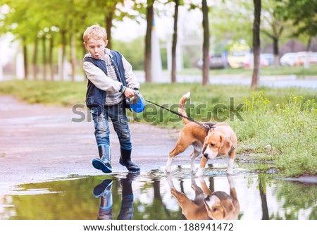 Little boy walk with his pet through the big puddle