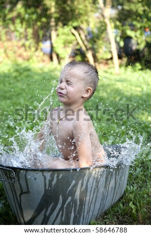 little boy washing in old washing tub outdoor - stock photo