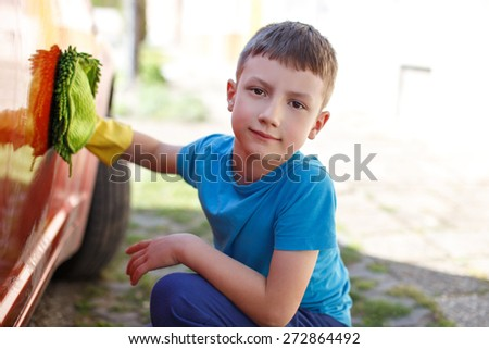 Little boy washing red car, outdoor portrait - stock photo