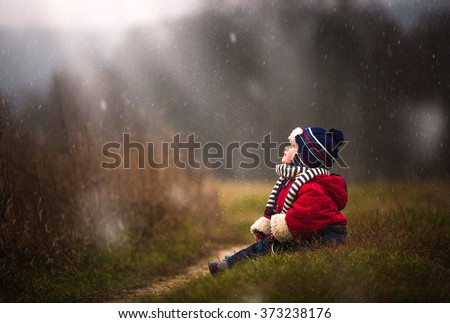 Little boy watching falling snow. Early winter caucasian child portrait. - stock photo