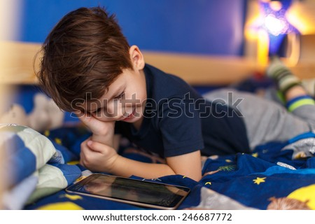 Little boy watching tales on tablet at home on bed - stock photo