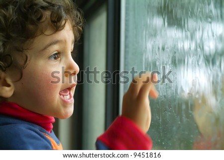 little boy watching the rain through the window - stock photo