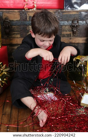 Little boy wearing a christmas suit looking at gifts - stock photo