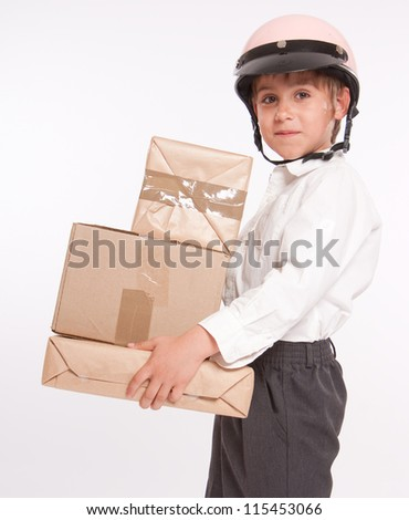 Little boy wearing a motorbike safety helmet holding a pile of boxes - stock photo