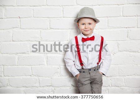little boy wearing a red bow tie, suspenders and white shirtand against a white brick wall. - stock photo