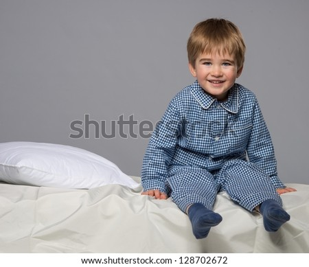 Little boy wearing blue pyjamas in bed - stock photo