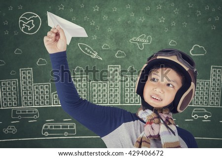Little boy wearing helmet and dreams of becoming an aviator while playing a paper plane - stock photo