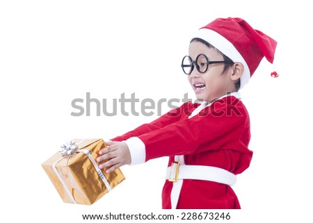 Little boy wearing Santa Claus uniform with a gift  - stock photo